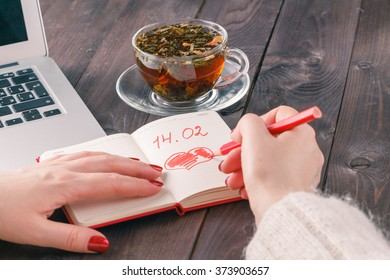 woman using laptop computer? and drawing red heart