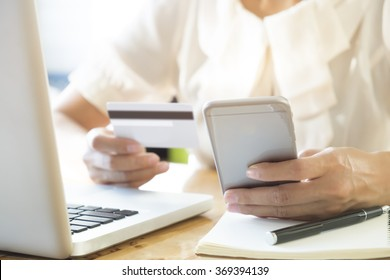 Woman using laptop and mobile phone to online shopping and pay by credit card. This picture is focus at woman's hand and use warm bright sunlight filter for feeling comfortable