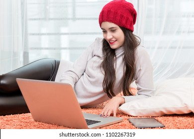 Woman Using laptop on the floor Drinking Coffee Enjoying Relaxing at cold winter day.