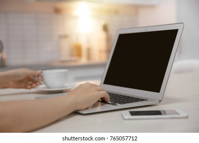 Woman using laptop on kitchen table