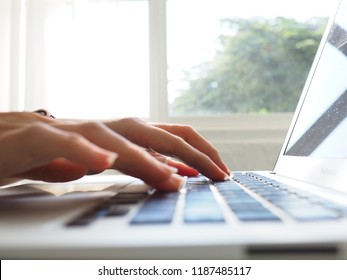 Woman using laptop on workplace close up