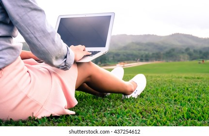 Woman using laptop in park.