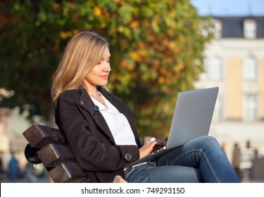 Woman using laptop sitting in the city street under colorful autumn trees