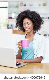 Woman using laptop while having coffee at home