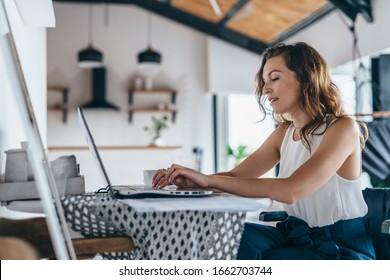 Frauen, die einen Laptop benutzen, während sie zu Hause sitzen. Junge Frau sitzt in der Küche und arbeitet auf dem Laptop.