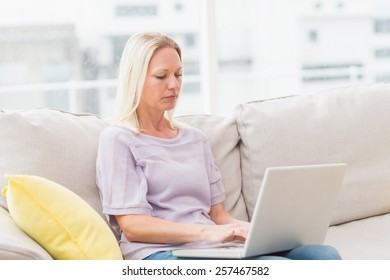 Woman using laptop white sitting on sofa in living room