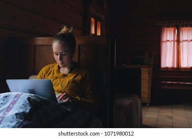 woman using laptop/smartphone in bed by window, rustic wooden cottage interior