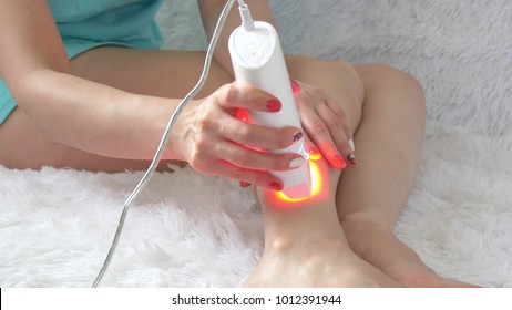 Woman using laser epilator for hair removal procedure at home - 4