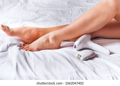 Woman using laser epilator or epilator for hair removal procedure at home