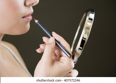 Woman using a lip pencil, looking at her reflection in a hand mirror