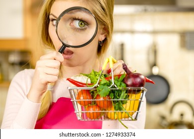 Woman using magnifying glass loupe, investigating shopping basket with many colorful vegetables. Healthy eating lifestyle, nutrients vegetarian food, searching for pesticides and chemicals.