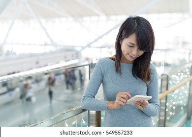 Woman using mobile phone at airport