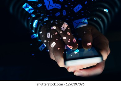 Woman using mobile phone for bulk text messaging in dark room interior, close up of hands typing sms