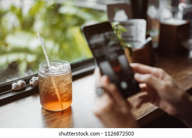 woman using a mobile phone capturing photos of ice tea for her blog.
