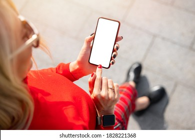 Woman using mobile phone with  empty white mockup screen, view from above