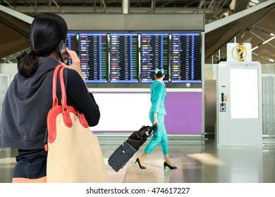Woman using mobile phone looking at flight timetable with flight attendants walking in airport as background