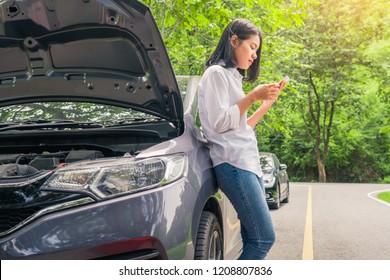 Woman using mobile phone near car