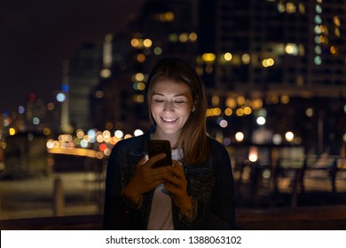 woman Using Mobile Phone At Night With City Skyline In Background