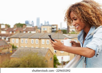 Woman Using Mobile Phone On Rooftop Garden Drinking Coffee