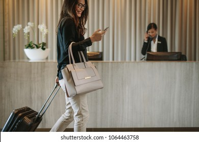 Photo of Woman using mobile phone and pulling her suitcase in a hotel lobby. Female business traveler walking in hotel hallway.