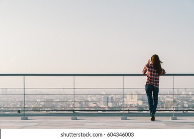 Woman using mobile phone at rooftop during sunset with copy space, communication or lonely people concept.