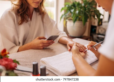 Woman using mobile phone in salon receiving a manicure and nail care procedure by beautician. Female getting nails done by manicurist at beauty salon.