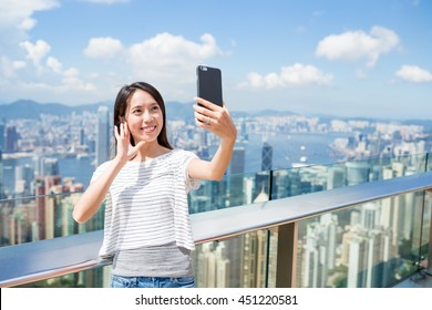 Woman using mobile phone to take photo in Hong Kong