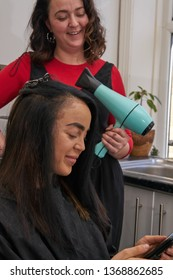 Woman Using Mobile Phone While Having Hair Styled