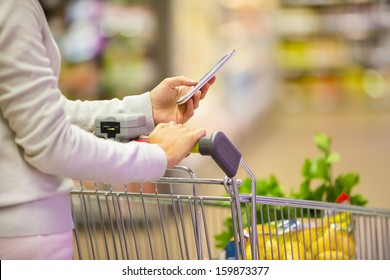 Woman using mobile phone while shopping in supermarket, trolley