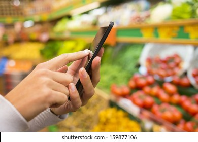 Woman using mobile phone while shopping in supermarket, vegetable department store