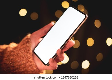 Woman using mobile smart phone at night with dramatic lighting, city lights and shallow depth of field. Blank screen with bright lighting for design mockups.