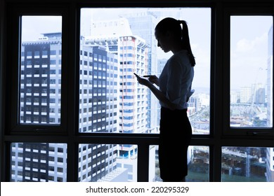 Woman using mobile smart phone in the office