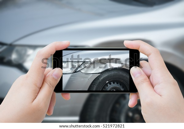 Frau, die Mobiltelefon verwendet, fotografiert Unfall beim Autounfall