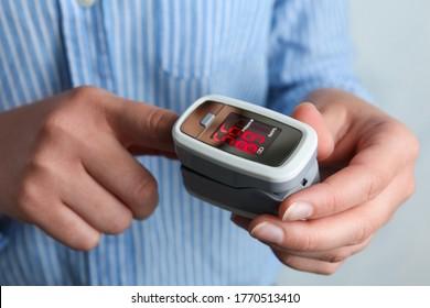 Woman using modern fingertip pulse oximeter on light background, closeup