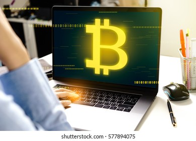Woman using modern laptop computer with Bitcoin .