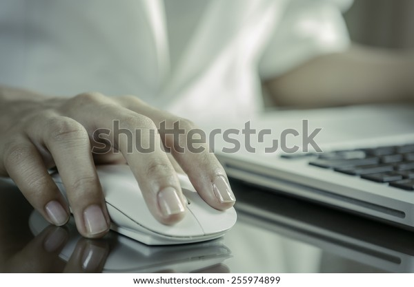 Woman using a mouse working on the computer