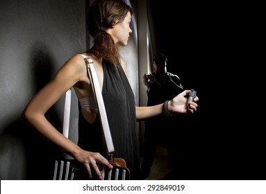 woman using a pepper spray for self defense against mugger in a dark alley.  She is using a canister of mace for security against a criminal.  The robber is hiding in the dark shadows.