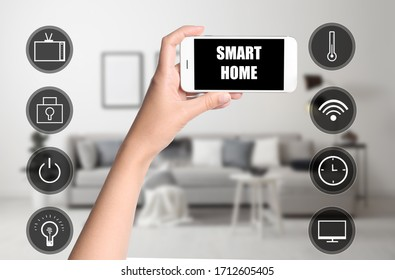 Woman using phone application for controlling smart home indoors, closeup