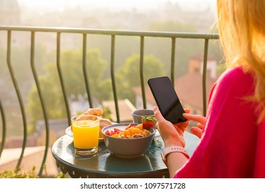 Woman using phone at breakfast on balcony