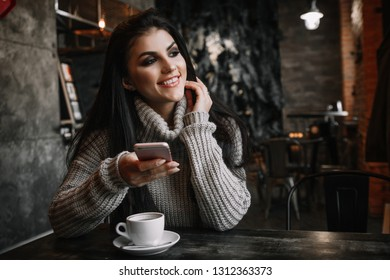 Woman using phone and drinking coffee in a cafe.