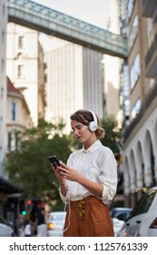 Woman using phone in european city while wearing headphones
