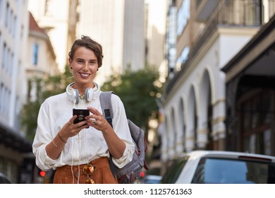 Woman using phone in european city