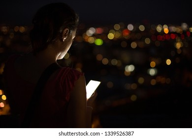 Woman using phone on roof top overlooking city at night