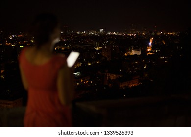 Woman using phone on roof top overlooking city at night. Focused on the city.