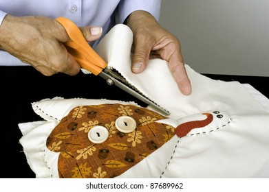 A woman using pinking shears to create a Thanksgiving turkey decoration.