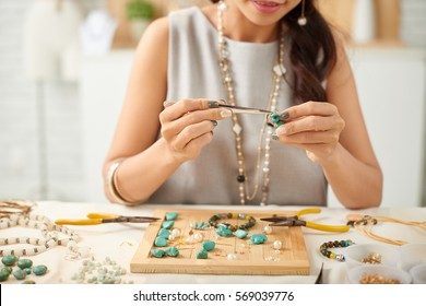 Woman using pliers to adjust malachite gemstones