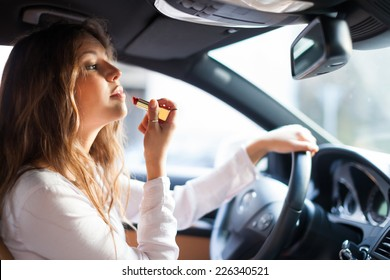 Woman using the rear-view mirror to apply make-up while driving her car