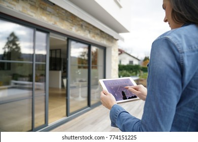 Woman using remote home control system on digital tablet
