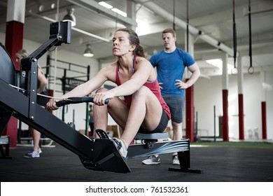 Woman Using Rowing Machine While Instructor Standing By