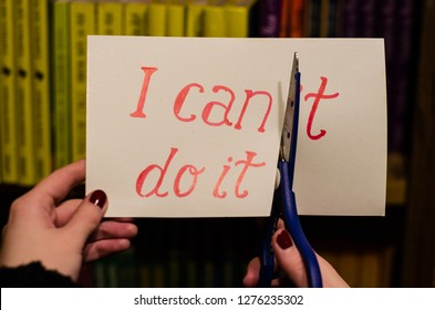 Woman using scissors to remove the word can't to read I can do it  on a shelf with books background, concept for self belief, positive attitude and motivation